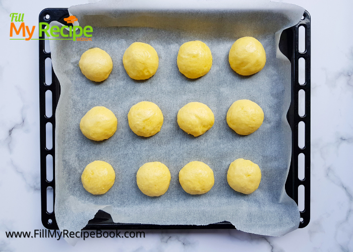 dough process of making small rolled balls on a baking tray of cream cheese kolache