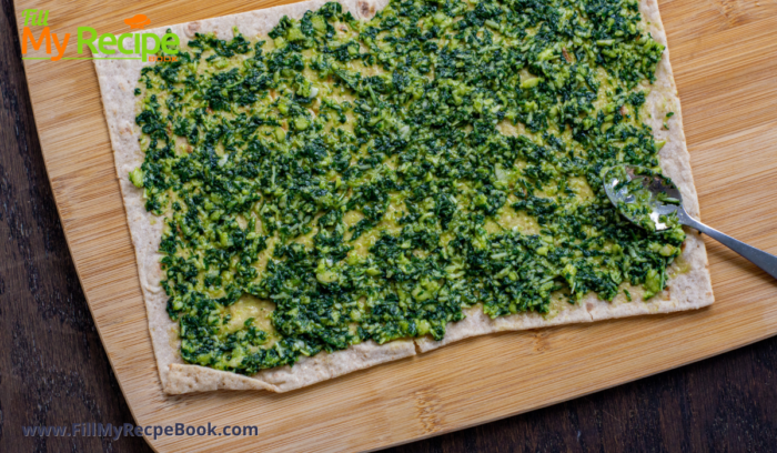 the flatbread getting spread with some basil pesto