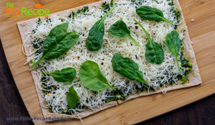 garnishing the flatbread with basil leaves