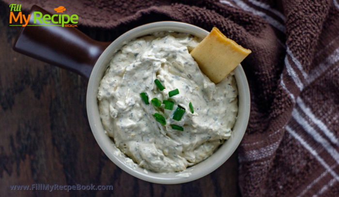 crackers and green onion dip in a bowl with snacks